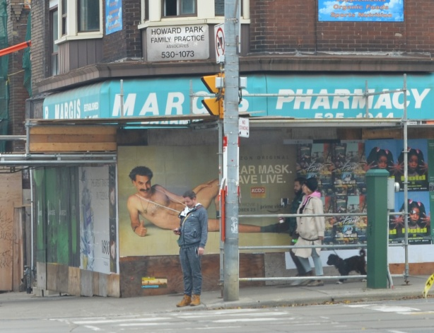 a man stands at an intersection waiting for traffic lights to change, he's in front of Borat poster, wear a mask, save live, man sands where he covers the mask