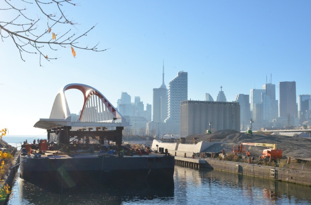 new Cherry street bridge on a barge in the Keating channel, just arrived from Nova Scotia, CN Tower and Toronto skyline in the distance