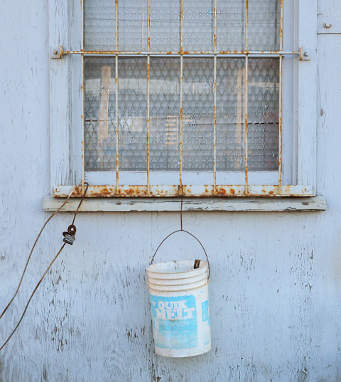 a window with on old rusty metal grille covering it, and a white bucket hanging by a chain