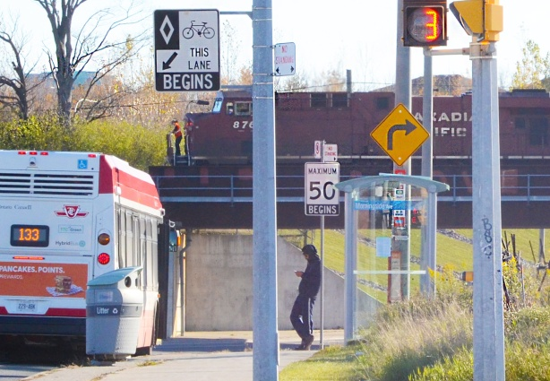 Canadian Pacific railway engines pass over bridge over Finch Ave. A TTC bus is waiting in the foreground, as well as a man standing at the bbus shelter.