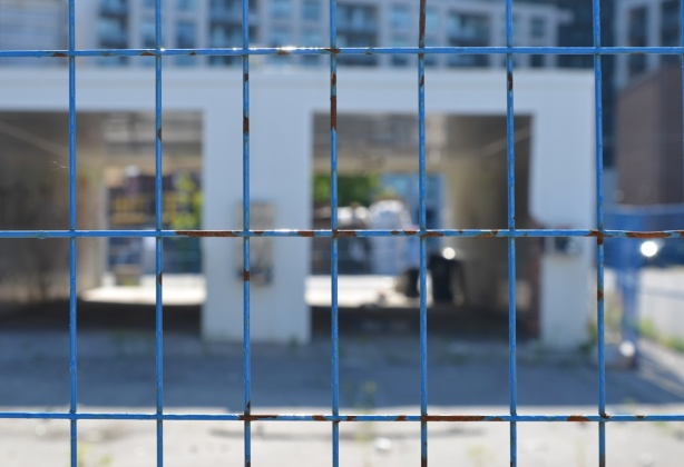 blue metal constructioon fence in the foreground with out of focus building behind, an old abandoned car wash