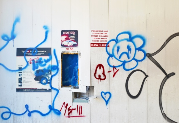 graffiti in red and blue on the interior walls of an old abandoned and emptied car wash, blue daisy frowny face