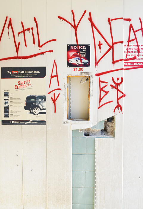 graffiti in red on the interior walls of an old abandoned and emptied car wash