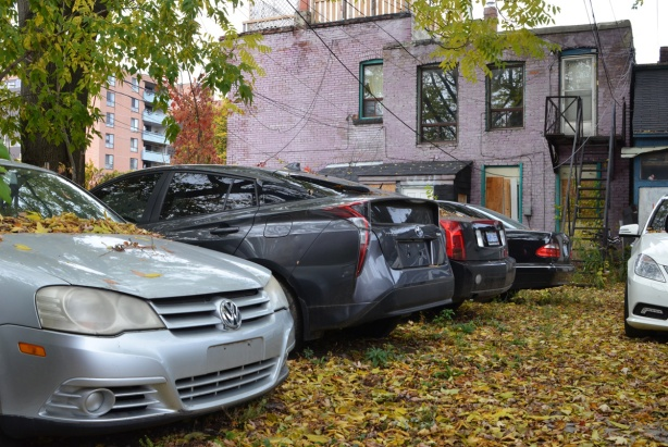 cars without licence plates parked behind an old building, alley,