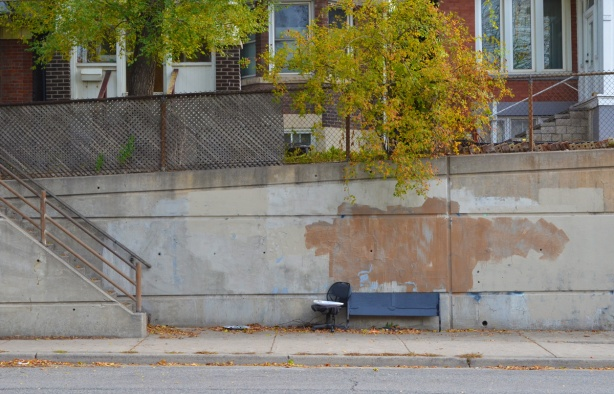 an old office chair beside a bench on the sidewalk