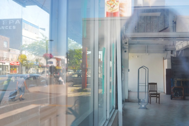 looking through a large window of a store to see almost empty interior, a chair is there along with a rack for hanging clothes. people and cars are passing by on the street