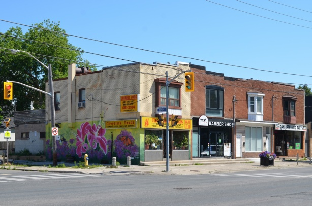 northeast corner of Danforth and Byng in Scarborough, a row of four brick two storey storefronts with apartments above. Chopsticks restaurant is on the corner, it has a large mural along its west wall, flowers and a monarch butterfly. Next to restaurant is a barber shop and then an empty store. Danforth Auto Parts is at the east end