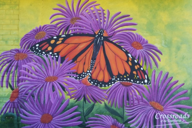 from a mural, monarch butterfly in the middle of purple asters flowers