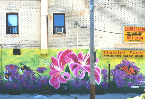 pink lilies in a mural with purple flowers and butterflies painted by De Anne Lamirande, at the corner of Danforth and Byng in Scarborough