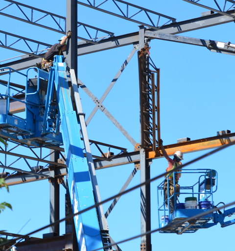 two men in lifts working high up on metal beams on a construction site