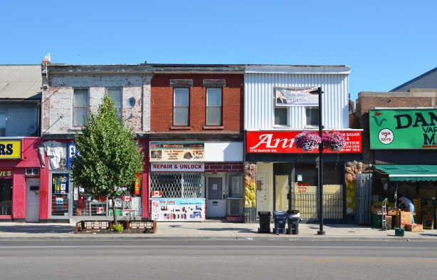 a row of three two storey brick stores on the Danforth.  Flat roofs, one in the middle is a computer repair shop.  A small tree covers the front of one store, Danforth market is on the far right