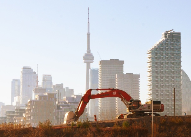 in the foreground, a red digger digs soil in the port lands, the CN Tower and toronto skyline in the distance