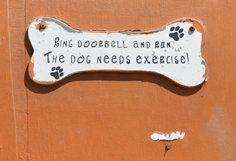 sign in the shape of a dog bone, on a door, that says ring doorbell and run, the dog needs exercise