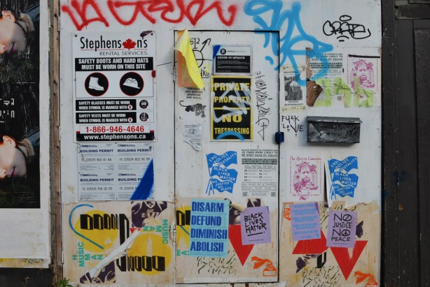 construction hoardings with a door on it, posters have been glued onto the wood
