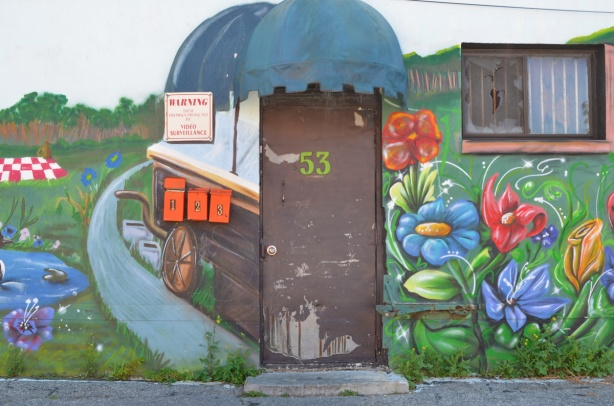 door with old blue awning above it, in the middle of a mural, 3 bright orange mailboxes beside the door