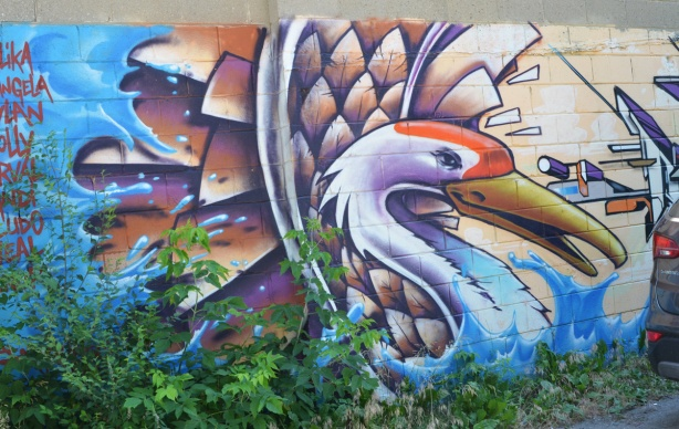 mural of a swan with a list of names to the left and a piece by mediah to the right