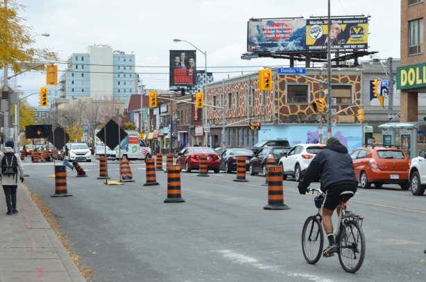 cyclist riding by construction on bloor street approaching dundas