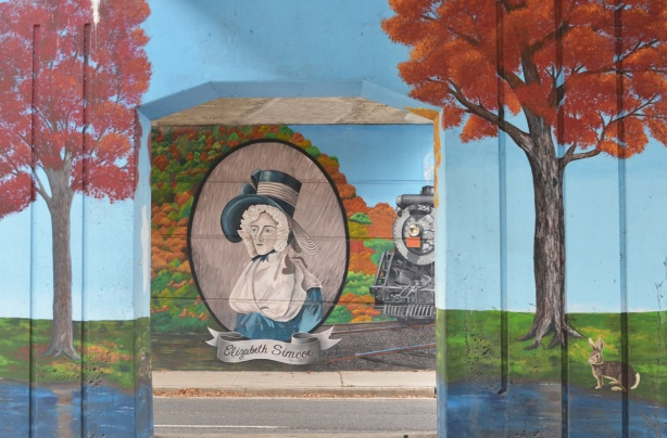 mural by De Anne Lamirande, portrait of Elizabeth Simcoe, in blue dress with white collar, large hat,