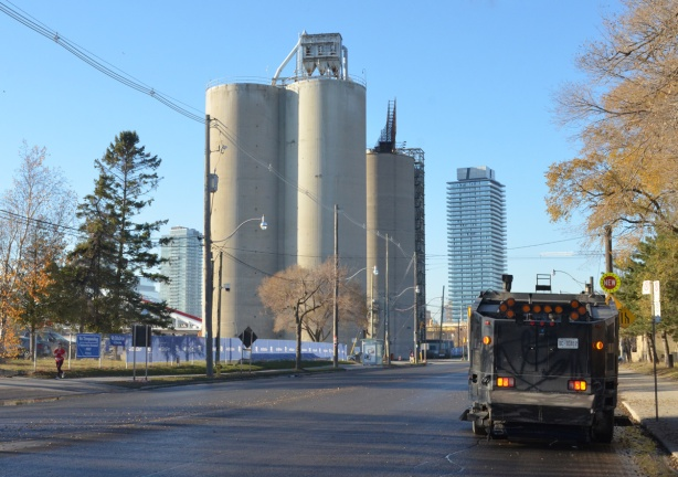 three tall silos that were part of essroc cement plant, now a heritage site in the port lands, a street cleaner is parked on the road, two condo towers in the distillery district can be seen in the background