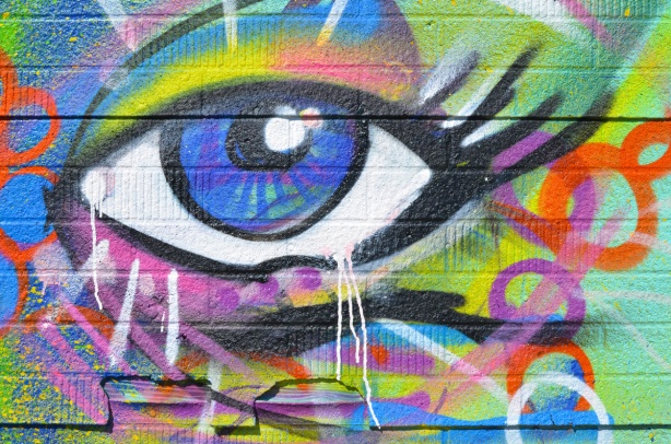 part of a street art mural, a big eye, blue in the middle