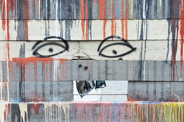 dripping paint in blue and red on a wall with a hole in it, two eyes drawn above the rectangular hole. A car is parked on the other side of hte wall and shows through the hole