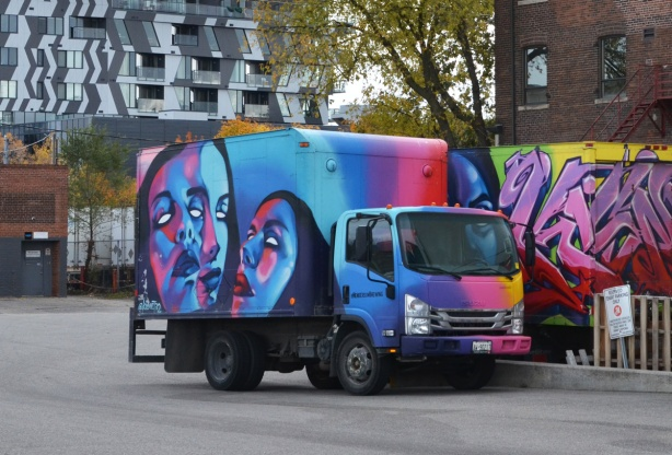 Henderson Brewery delivery truck covered with street art by kizmet, 3 faces in shades of blue, purple, pink, and turquoise