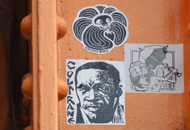 three stickers on orange metal support of west toronto railpath bridge over Bloor. One is a portrait of a black man Coltrane, another is a feelings boi sticker and last is a sticker that is feelings boi along with urban ninja squadron,