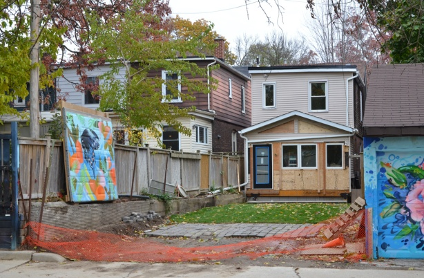 a house, seen from the back, being renovated, backyard is also being fixed up, fence between house and park has been removed, but garage door with mural on it has been preserved