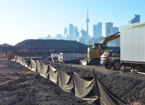 draped black fabric forms a fence at a construction site, CN Tower and Toronto skyline in the distance