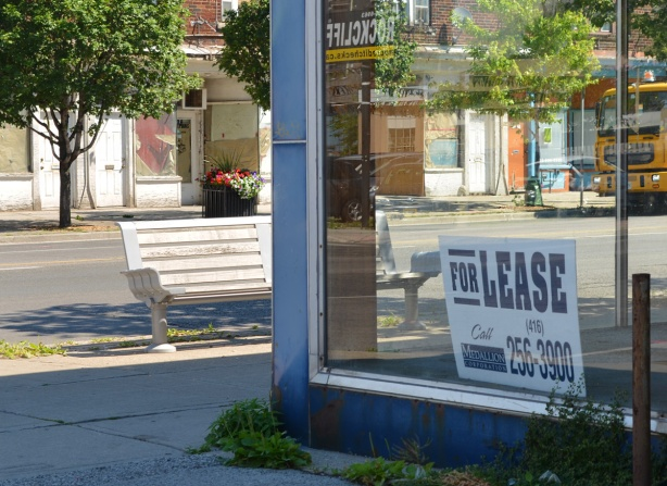 empty store, for lease sign in the window, looking trhough to other side of street, as well as reflections from window, white bench on sidewalk, yellow truck parked on street