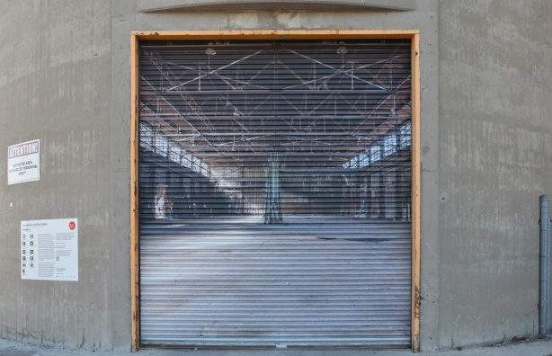large photo of an empty old warehouse mounted on an exterior metal door