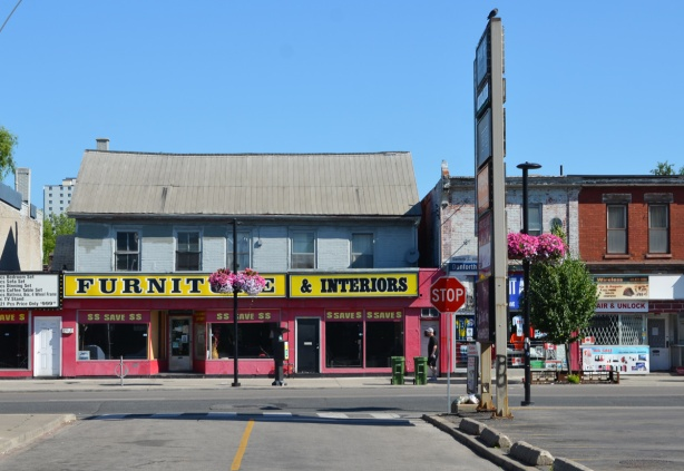 furniture store in old two storey building on the Danforth   with three big windows with save $ $ signs, old building with sagging roof.