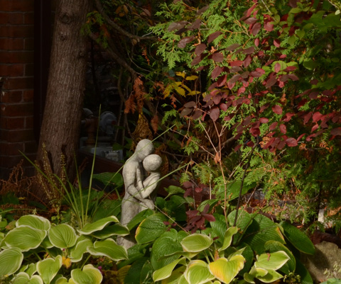 small statue of a couple embracing in a garden in a front yard