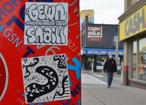 2 graffiti stickers on a Canada Post box, the top ones says gewn snail, the bottom one is an abstract drawing in black and white