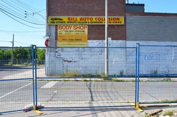 blue metal construction fence, empty parking lot beside building with a sign on it that says Gill Auto Collision