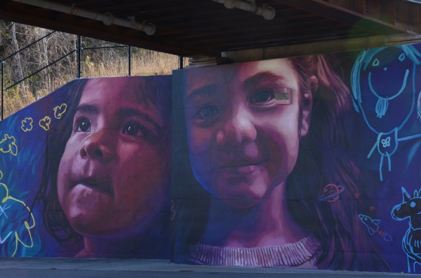 mural, two large girls faces, under a railway bridge, on Morningside, by Lacey and Layla