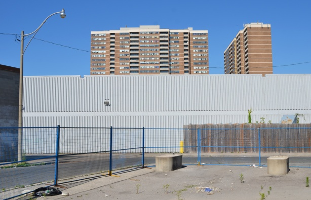 tall apartment buildings behind a tall plain grey wall, a street in front and then a vacant lot that's been paved over