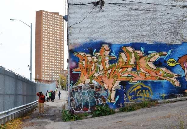 highrise apartment building in the background with a concrete building with lower level covered by street art in the foreground, people walking in the alley behind the concrete building