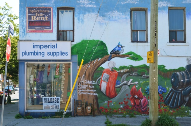 on the side of a now empty Imperial Plumbing store is a mural by Basil Dwayne Jardine jr of a scene