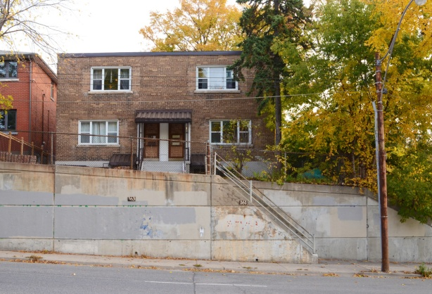 square, two storey brick duplex on a hill, with concrete wall in front, lots of steps going up