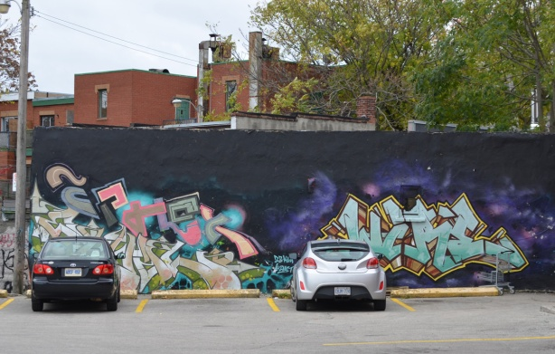 two cars parked in front of a kizmet mural