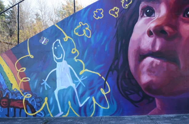 part of a mural by Lacey and Layla called Colour Outside the Lines, a young girl looking upward, a child's drawing of a girl in with a curly yellow line around it