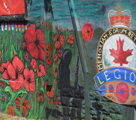 a black silhouette of a soldier kneeling, the Royal Canadian legion crest and motto lots of red poppies in flanders fields on a mural beside a legion hall, also a row of medals painted under a window