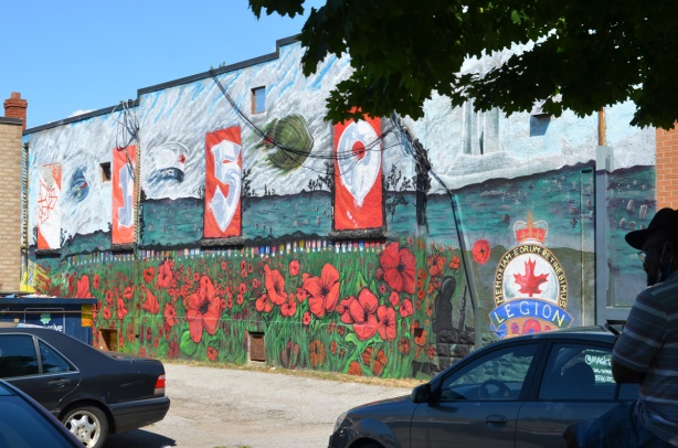 cars parked and a man sitting in front of mural in the side of Royal Canadian Lion branch 73, Oakridge Branch, poppies, a yellow airplane, beside an alley,
