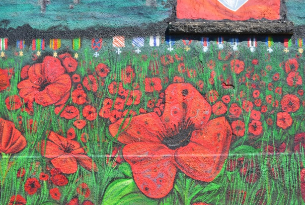 lots of red poppies in flanders fields on a mural beside a legion hall, also a row of medals painted under a window