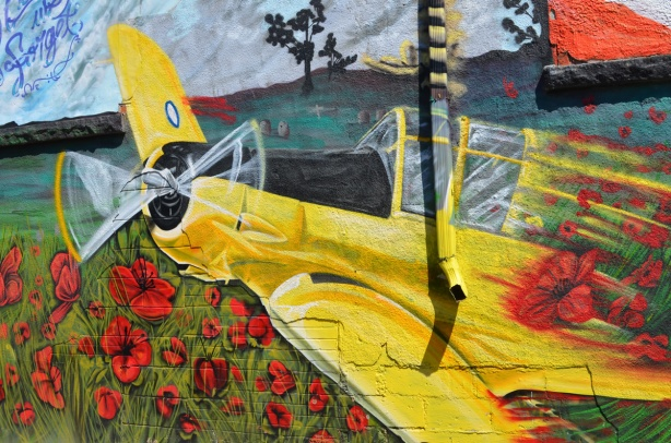 a yellow airplane, single jet, open cockpit, in a mural by magic f wong