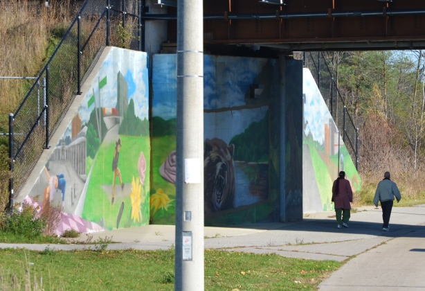 two people walk past a mural on a railway underpass