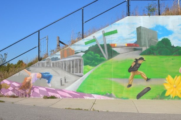 end of a mural underpass, sloped concrete with railing on top