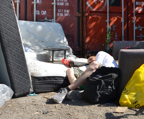man aslepp outside on a grey chair and old mattress, red container bins behind him