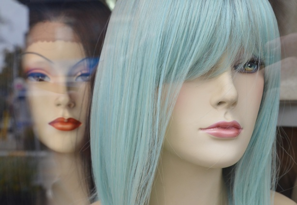 two wig mannequin heads in a store window. the one in front has pale turquoise hair, the one in the back has black hair.